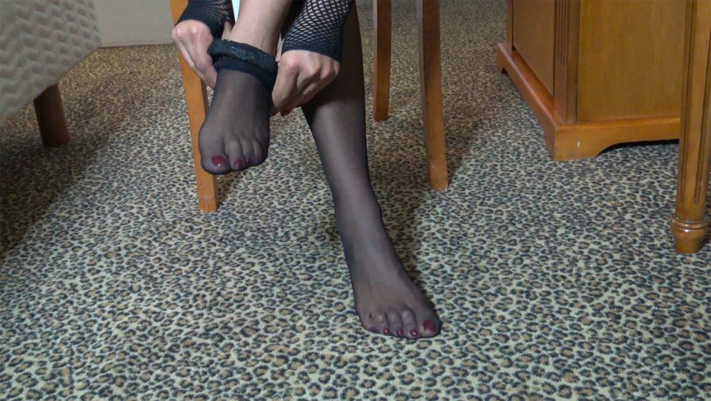 An ebony dominatrix puts on black stockings