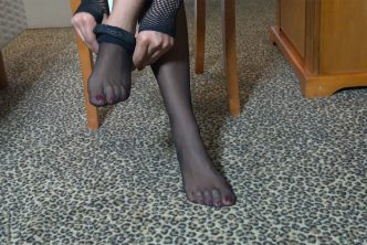 An ebony dominatrix puts on black stockings