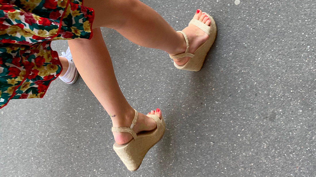 A girl with a tattooed ankle and wedge sandals